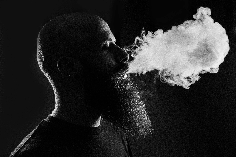 Man blowing vape cloud.