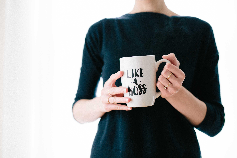 Woman holding Like a Boss mug.