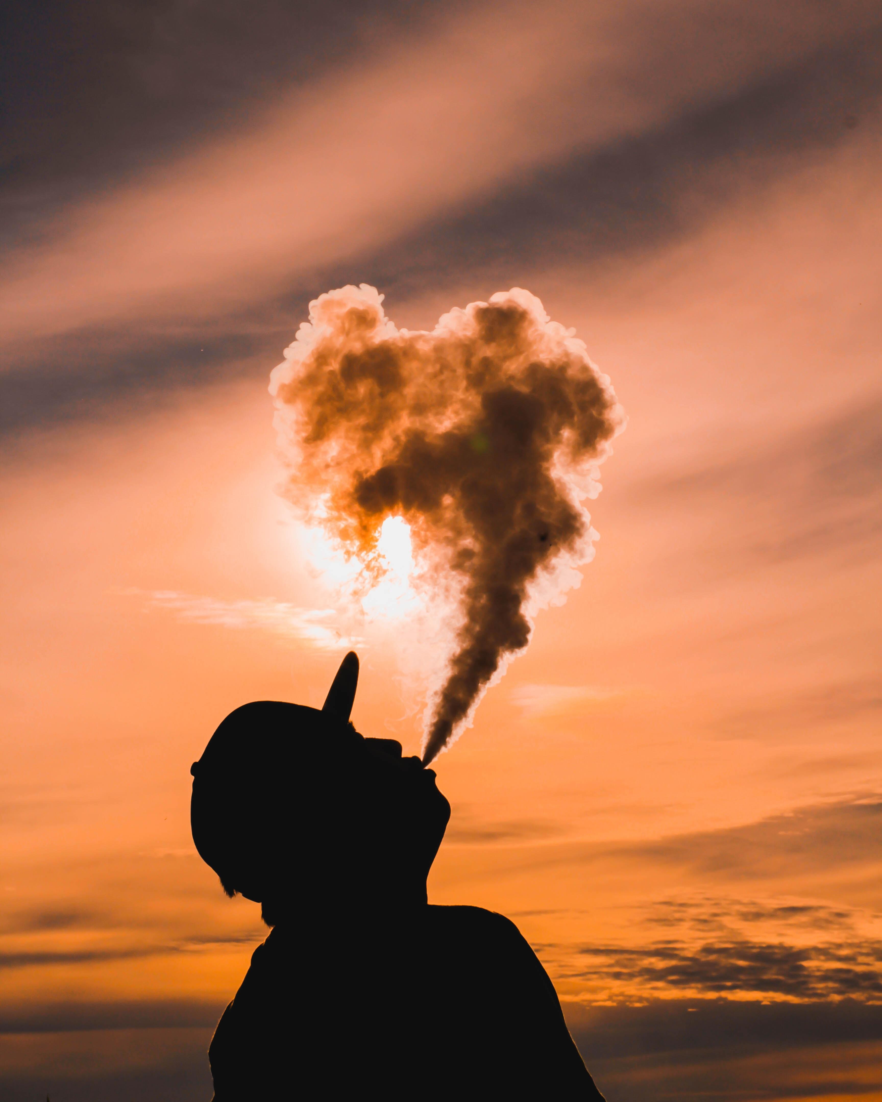 Man blowing vape smoke.